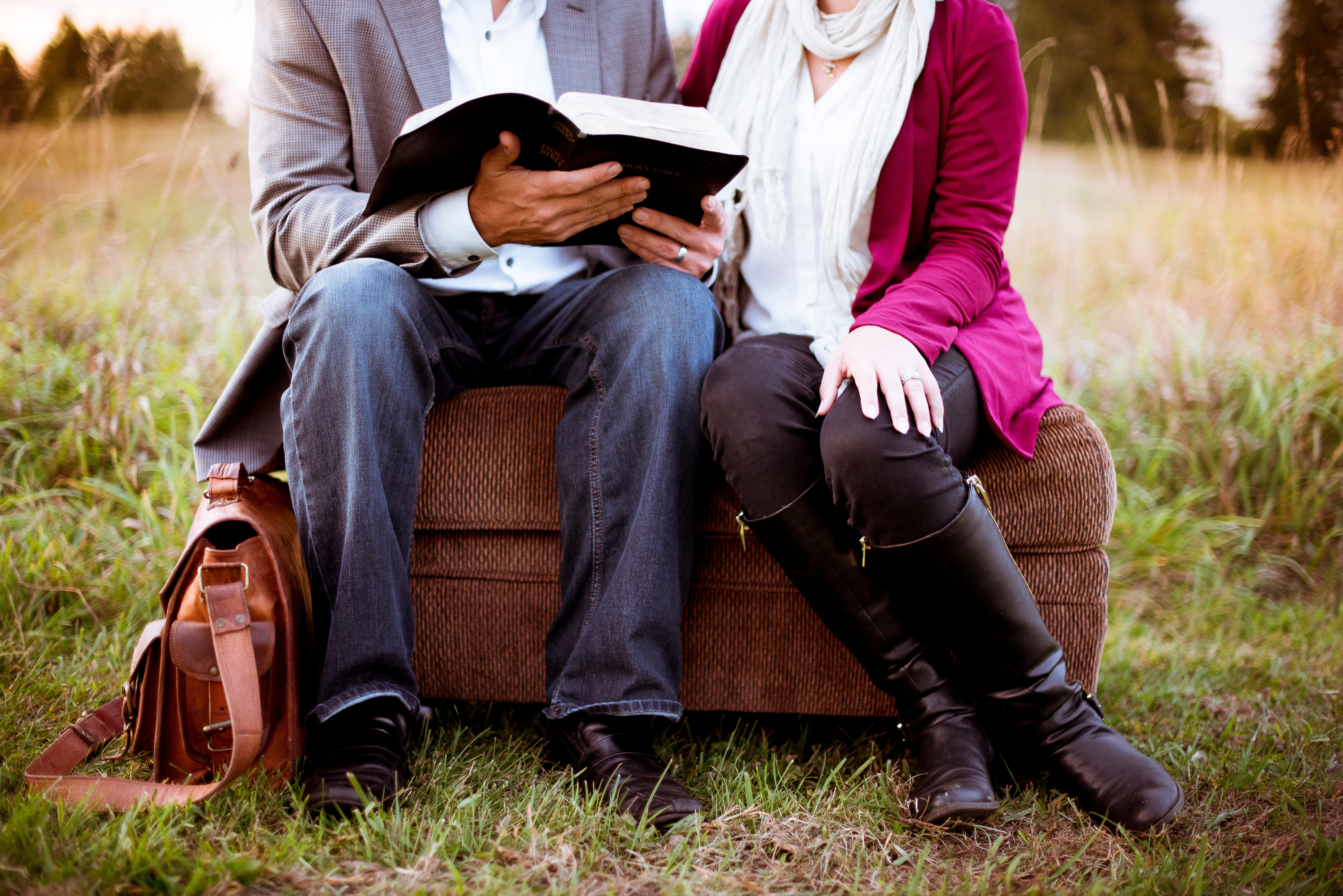 A couple, sat on an ottoman, reading from a leather bound book in a meadow